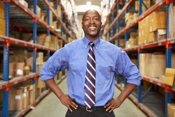 Portrait Of Businessman In Warehouse Standing With Hands On Hips Smiling