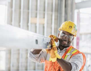 A mid adult African-American man in his 30s wearing a hard hat, protective goggles, a safety vest and work gloves, carrying a piece of construction material into the structure being built. The construction worker is smiling, looking at the camera.